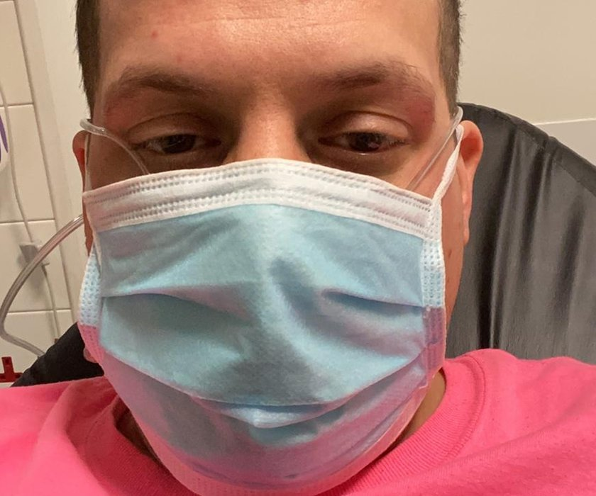 Dan Eggerton is looking at the camera he is wearing a pink t-shirt and a surgical face mask.