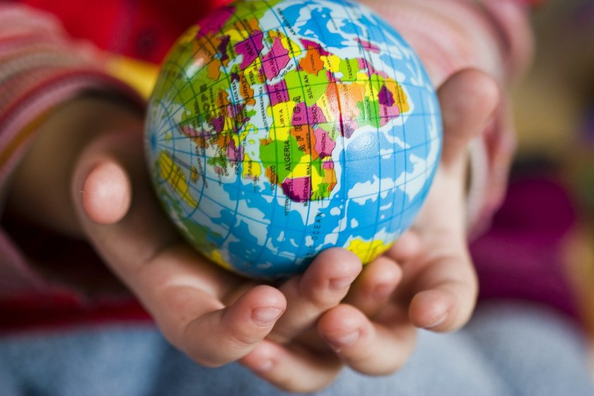 A child's hand holding a globe
