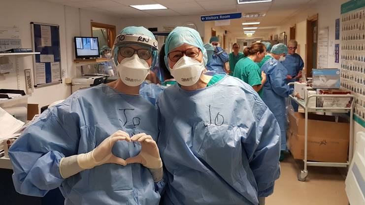 Two members of staff in PPE, one using their hands to make a heart