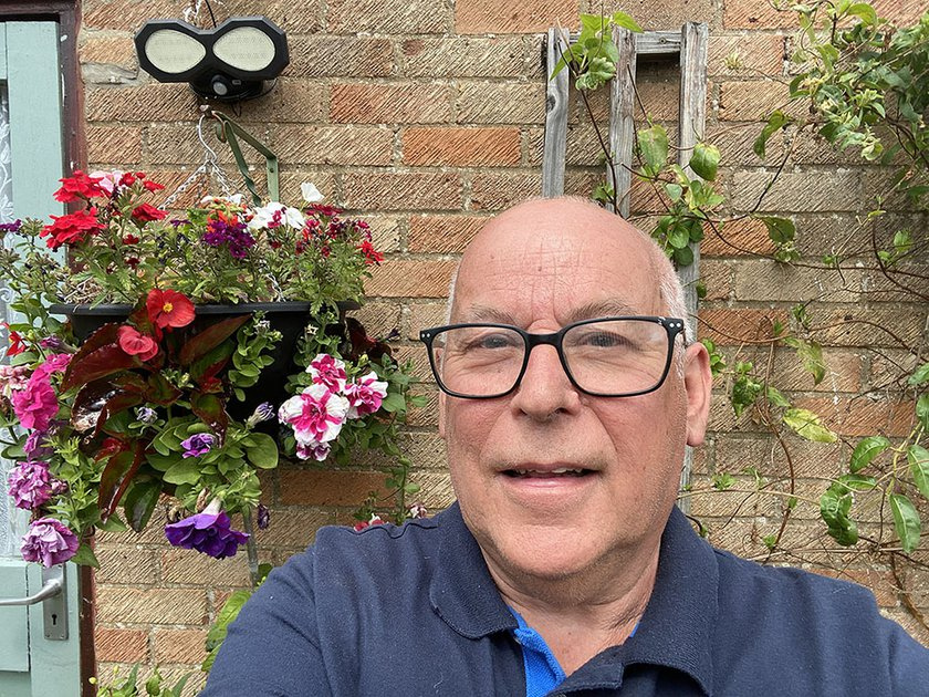 Head shot of our patient Pete Herring smiling at the camera. He is outside with a brick wall background and a hanging flower basket next to him.