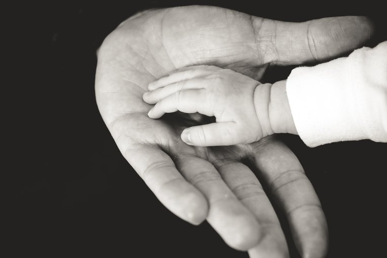 New born child hand in hand with adult hand