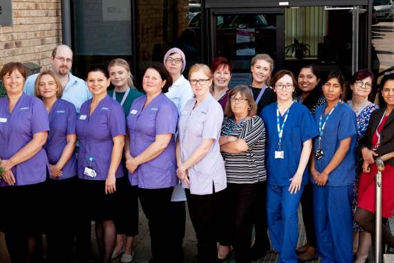 Team photo of staff at Cambridge IVF, taken outside Kefford House.