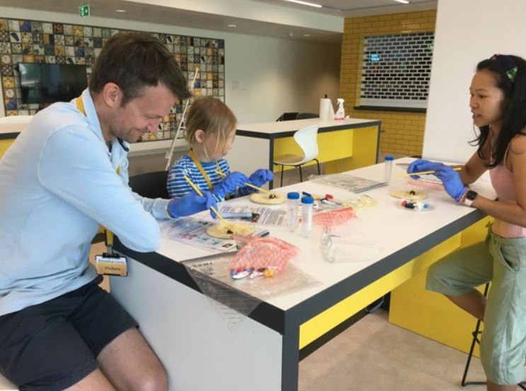 Molly and her dad are sat at a table in one of the research labs taking part in an activity that learns about microbiology