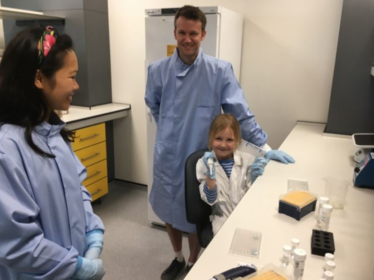 Molly is sat on a chair caring out a mock experiment she is wearing a white lab coat and smiling at the camera. Her dad and a member of our staff is with her they are both standing up smiling in blue lab coats.