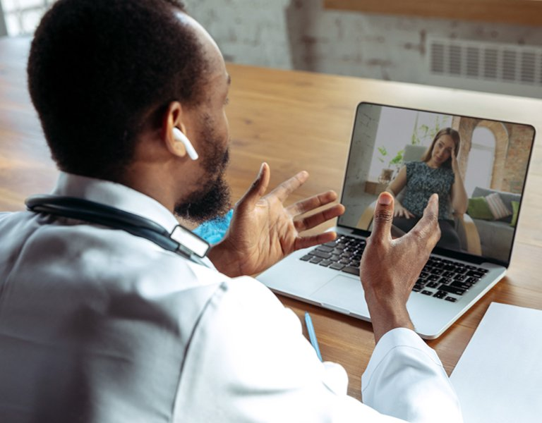 Patient having an online consultation with a doctor who is using a tablet.