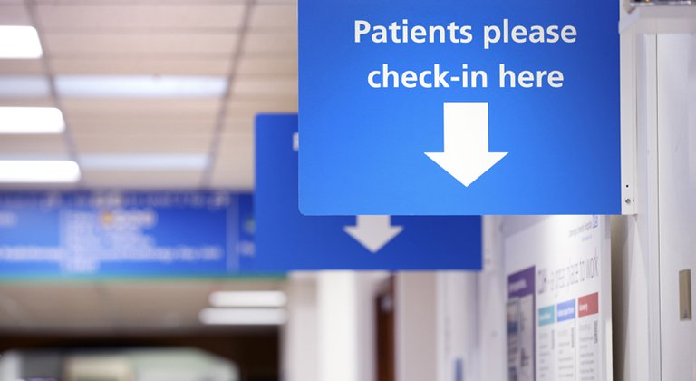 Patient check-in sign on wall in outpatients waiting area