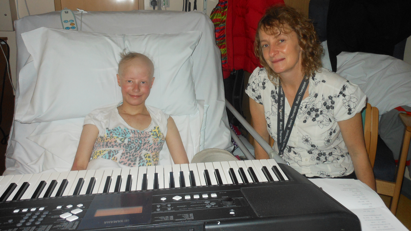 Patient Jess with her music therapist Clare Rosscornes. Jess is sitting up in bed with a keyboard on her lap.