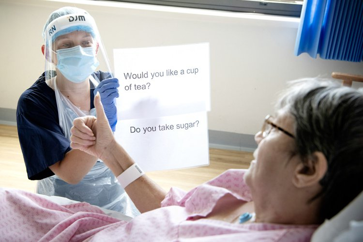 A nurse using a sign to communicate with a patient during covid-19 pandemic.