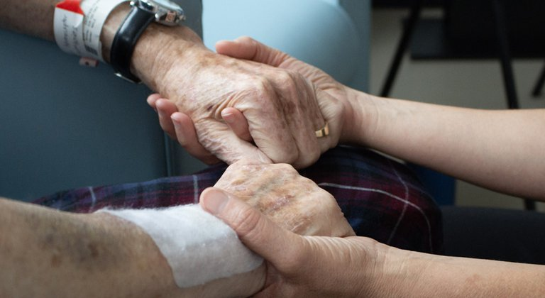 A patient holding hands with another person during a visit